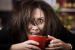 4190666-half-awake-woman-cradling-a-mug-of-coffee